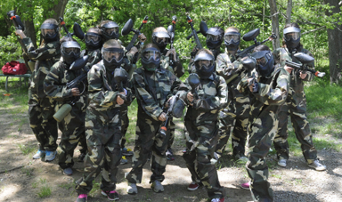 a group of kids in camouflage and paintball gear posing for a photo