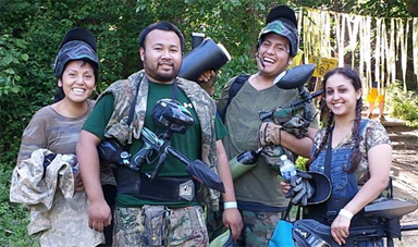 four smiling people in paintball gear